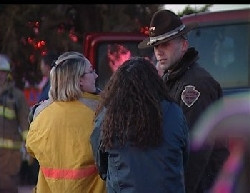 Women talk with emergency personnel at the site of a fire.