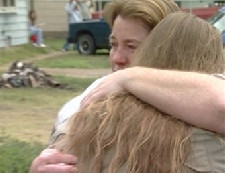 Women embrace after a tornado has ravaged their home.
